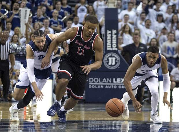 Fresno State guard Christian Gray (11), Nevada forward Cody Martin, left, and forward Tre'Shawn Thurman, right, scramble for a loose ball in the second half of an NCAA college basketball game in Reno, Nev., Saturday, Feb. 23, 2019. (AP Photo/Tom R. Smedes)
