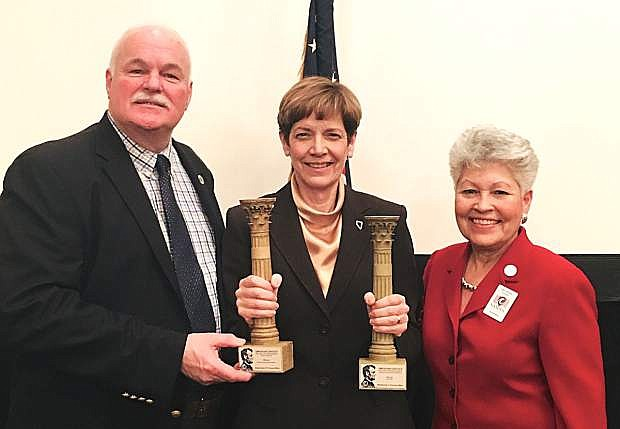 VA Undersecretary of Memorial Affairs, Robert Wilkie, left, and the president of NASDVA, Alfie Alvarado, right, stand with NDVS Director Kat Miller as she holds two Abraham Lincoln Pillars of Excellence Awards.