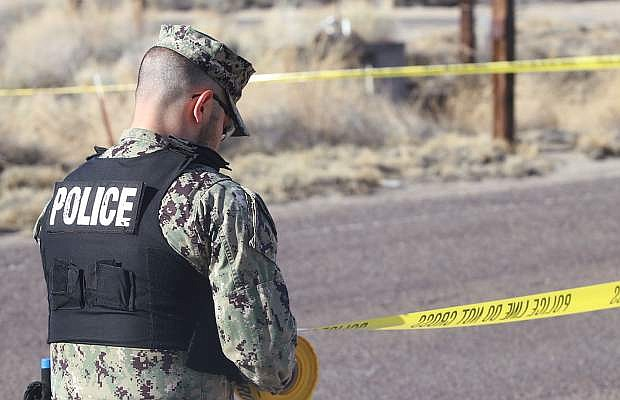 A law enforcement officer cordons off an area with tape.