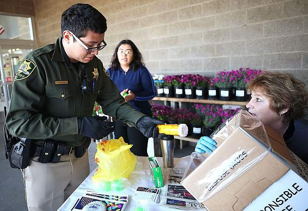 Carson City Sheriff's Reserve Deputy Tulio Marroquin and volunteer Jenny Smith process unused drugs collected during a Partnership Carson City Drug Roundup in 2018. The next roundup is April 27.