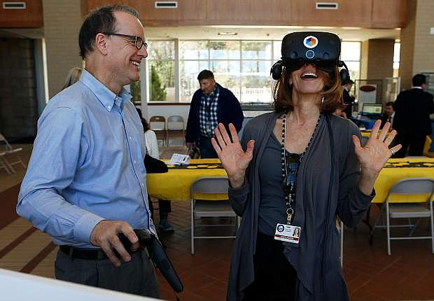 Mark Anderson, with Lifeliqe, introduces Janet Lazarus to an educational virtual reality program during the Nevada Library Legislative Day luncheon at the Nevada State Library, Archives and Public Records in Carson City, on Thursday.