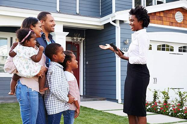 Real estate agent showing a family a house.