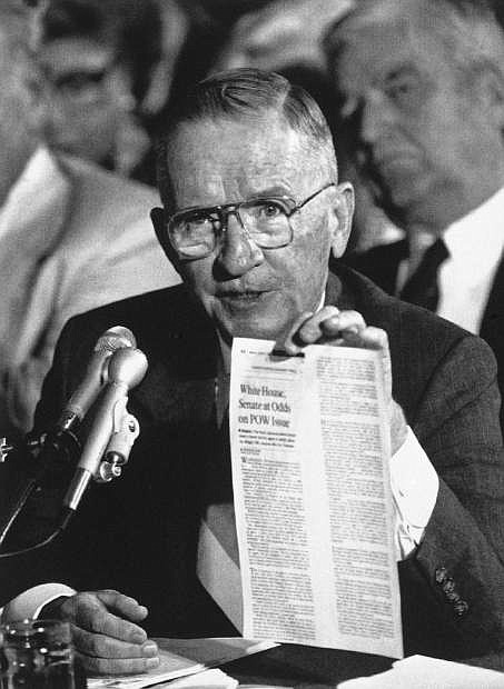 FILE - In this Aug. 11, 1992, file photo, Ross Perot holds up a newspaper article as he testifies before the Senate Select Committee on POW-MIA Affairs on Capitol Hill, in Washington. Perot said he believes some American prisoners may have been left behind after the Vietnam War. Perot, the Texas billionaire who twice ran for president, has died, a family spokesperson said Tuesday, July 9, 2019. He was 89.  (AP Photo/J. Scott Applewhite, File)