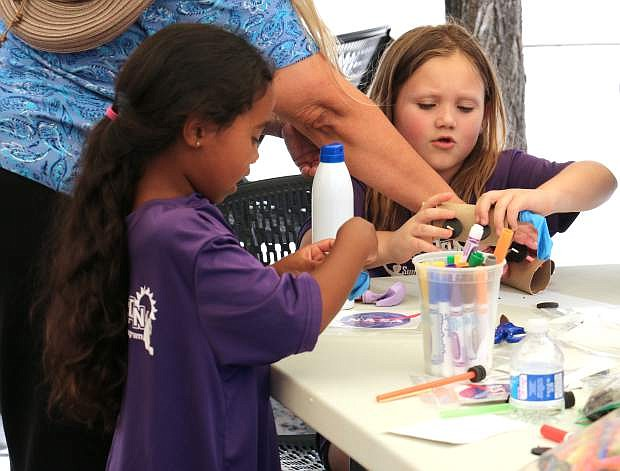Nevada State Museum volunteers help children to build and test balloon-powered rocket cars in the Nevada State Museum's parking lot Wednesday.