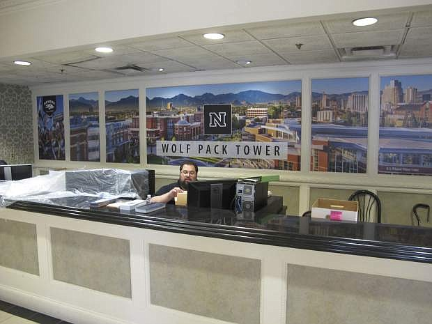 In this Monday, Aug. 19, 2019 photo, a University of Nevada, Reno, employee oversees the desk in the lobby of a Circus Circus casino hotel tower in downtown Reno, Nev., that has been converted into a dormitory a half-mile from the main campus. Now called Wolf Pack Tower, it will house about 1,300 UNR students for the coming school year after a July gas explosion shut down the two largest dorms. (AP Photo/Scott Sonner)