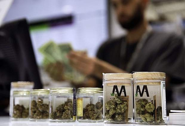 FILE - In this July 1, 2017, file photo, a cashier rings up a marijuana sale at a cannabis dispensary in Las Vegas. Attorneys for Nevada and some companies that won retail marijuana dispensary licenses last year say mistakes might have been made, but tax officials are fairly enforcing a voter-approved initiative that legalized recreational marijuana. Steve Shevorski, a top deputy state attorney general, told a judge in Las Vegas on Friday, Aug. 16, 2019, there would be no basis for her to issue an order blocking licensees from opening new stores statewide until a trial is held. (AP Photo/John Locher, File)