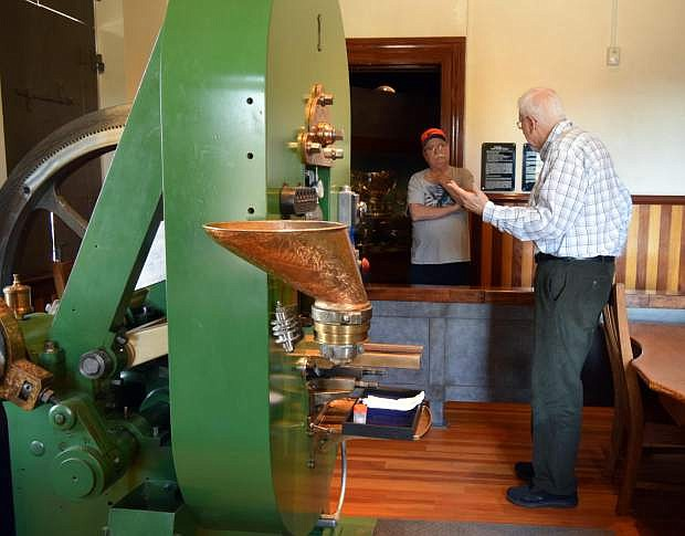 Bob Nylen, right, curator of history at the Nevada State Museum, gives a museum visitor a brief history of Coin Press No. 1.