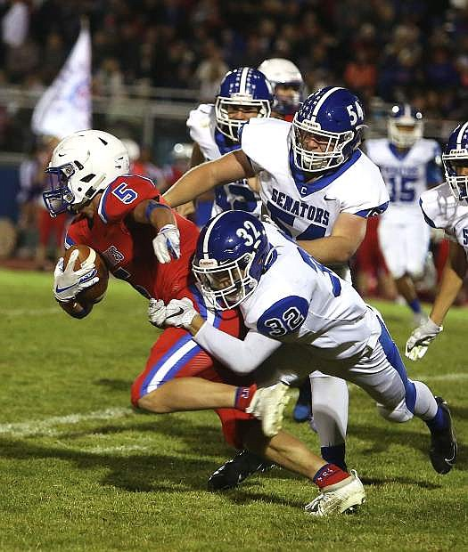 David Leach (32) and Connor David (54) wrap up Reno running back Drew Worthen last week in the Senators' road game against the Huskies. Reno topped Carson 34-17.