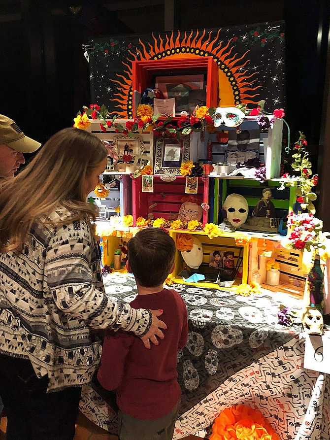 A family takes a look at one of the altars created for the annual Day of the Dead Community Celebration at the Nevada State Museum.