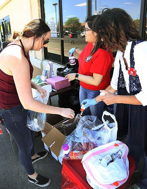 Partnership Carson City's Samantha Szoyka, left, and Diana Alonzo, as well as Lisa Bitler, put unused medication into containers during the PCC Drug Round-up in April. The community safety event, held in April and October every year, netted 414 pounds of pills and 137 pounds of needles.