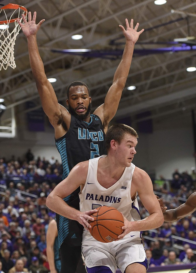 FILE - In this Dec. 15, 2018. file photo, Furman's Matt Rafferty works against North Carolina Wilmington's Jeantal Cylla during the first half of an NCAA college basketball game in Greenville, S.C. Eric Musselman, the new coach at Arkansas, relied heavily on transfers at Nevada and bolstered his new team with graduate transfers Cylla from UNC Wilmington and Jimmy Whitt Jr.