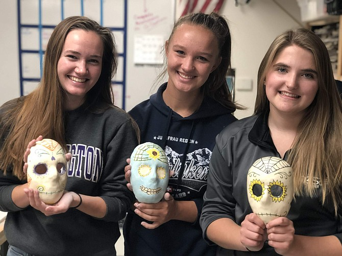 CHS seniors Elizabeth Schulze, 18, Sophia Taggart, 17, and Emma McCoy, 17, from teacher Alisa Kuniya's ceramics class display their Dia de los Muertos masks.