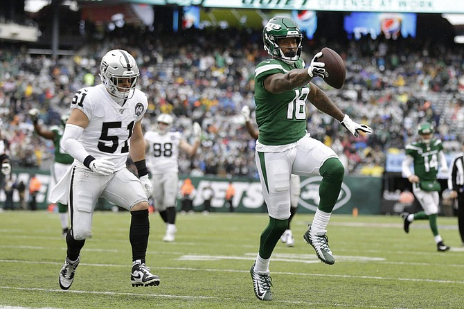 ADDS THAT THE TOUCHDOWN WAS LATER NULLIFIED BY PENALTY - New York Jets wide receiver Demaryius Thomas (18) runs away from Oakland Raiders inside linebacker Will Compton (51) for a touchdown during the first half of an NFL football game Sunday, Nov. 24, 2019, in East Rutherford, N.J. The touchdown was later nullified by penalty. (AP Photo/Adam Hunger)