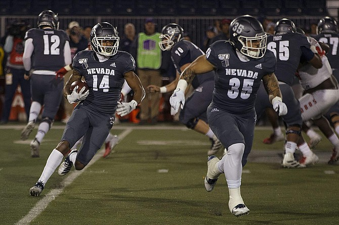 Nevada wide receiver Dominic Christian (14) follows the block of running back Toa Taua against New Mexico on Saturday at Mackay Stadium in Reno.