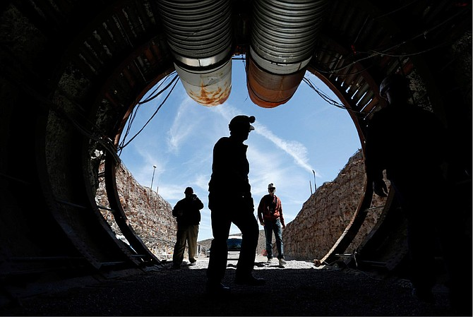 """FILE - In this April 9, 2015, file photo, people walk into the south portal of Yucca Mountain during a congressional tour of the proposed radioactive waste dump near Mercury, Nev., 90 miles northwest of Las Vegas. Nevada is branding federal shipments of weapons-grade plutonium to the state a year ago as a """"secret ... smuggling operation,"""" and urging a U.S. District Court judge in Reno to reject a bid to dismiss a lawsuit because the Energy Department has already promised no more material will be brought to the state. A court filing Monday, Dec. 16, 2019, seeks oral arguments in a yearlong legal battle over the state's bid for a court order to remove the highly radioactive material from a vast secure government reservation north of Las Vegas. (AP Photo/John Locher, File)"""