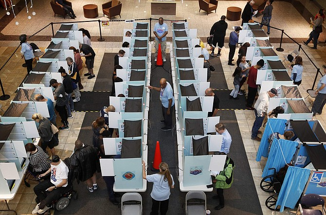 FILE--In this Nov. 6, 2018, file photo, people vote in Henderson, Nev. Advocates for creating a non-partisan commission to redraw Nevada voting districts instead of the Legislature are offering to amend a proposed statewide ballot initiative to appease a North Las Vegas pastor who has sued to block it. (AP Photo/John Locher, file)