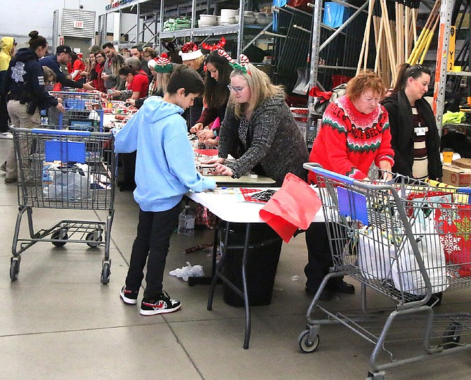 Carson City School District students bring the gifts they've just purchased to to have wrapped by volunteers Wednesday at Walmart at the Holiday for a Hero program.