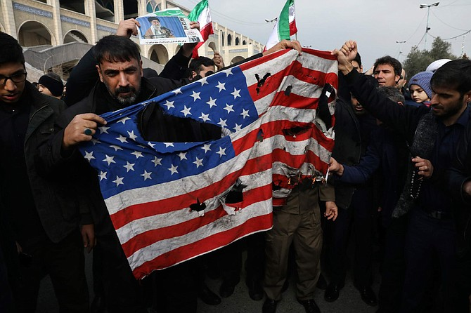 """Protesters burn a U.S. flag during a demonstration over the U.S. airstrike in Iraq that killed Iranian Revolutionary Guard Gen. Qassem Soleimani, in Tehran, Iran, Jan. 3, 2020. Iran has vowed """"harsh retaliation"""" for the U.S. airstrike near Baghdad's airport that killed Tehran's top general and the architect of its interventions across the Middle East, as tensions soared in the wake of the targeted killing. (AP Photo/Vahid Salemi)"""