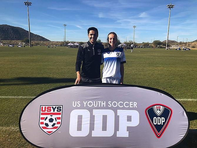 Douglas High girls soccer coach Andrew Robles poses behind an Olympic Development Program banner with Douglas freshman Camden Miller.