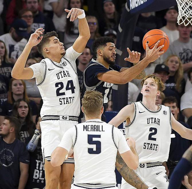 Nevada guard Jalen Harris (2) grabs a rebound against Utah State guards Diogo Brito (24), Sam Merrill (5), and Sean Bairstow (2) during the second half of an NCAA college basketball game Saturday, Jan. 11, 2020, in Logan, Utah. (Eli Lucero/Herald Journal via AP)