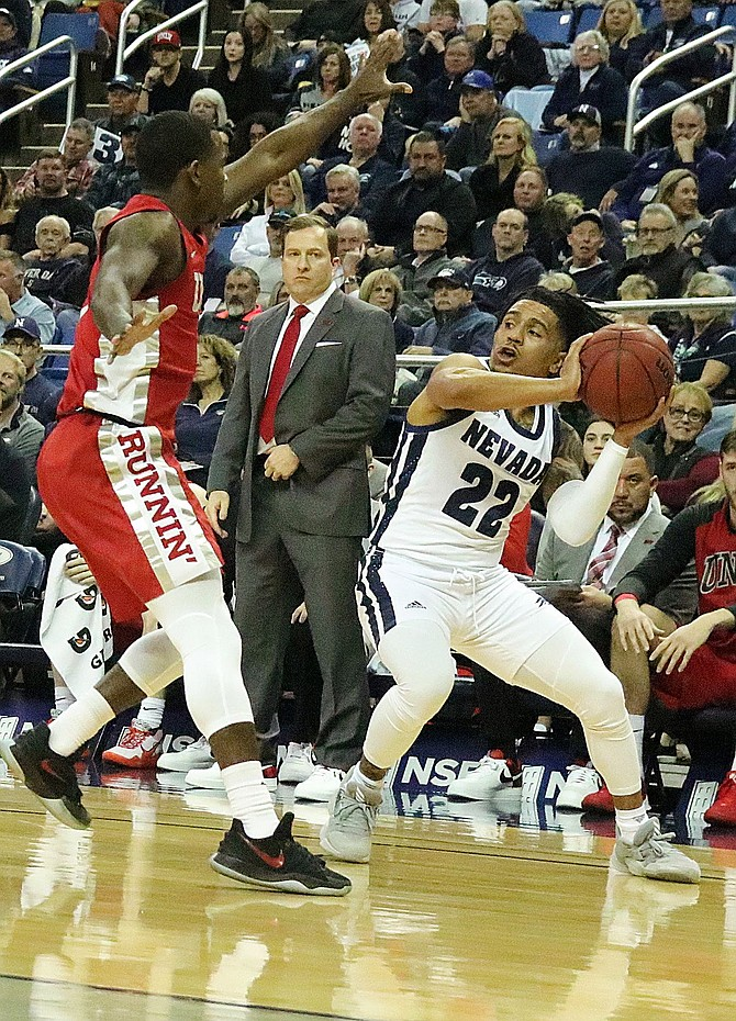 UNLV's Amauri Hardy guards Nevada's Jazz Johnson the corner by the Rebels bench in Wednesday's Mountain West Conference game.