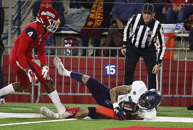 Nevada wide receiver Elijah Cooks dives in for a touchdown as Fresno State defensive back Wylan Free gives chase in Fresno, Calif., on Nov. 23. Cooks and Romeo Doubs combined to catch 185 passes for 2,485 yards and 20 touchdowns over the past two seasons.