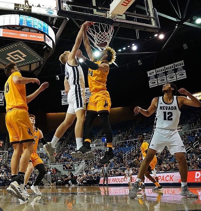 Nevada's Zane Meeks dunks over Wyoming's Hunter Maldonado in the first half on Tuesday.