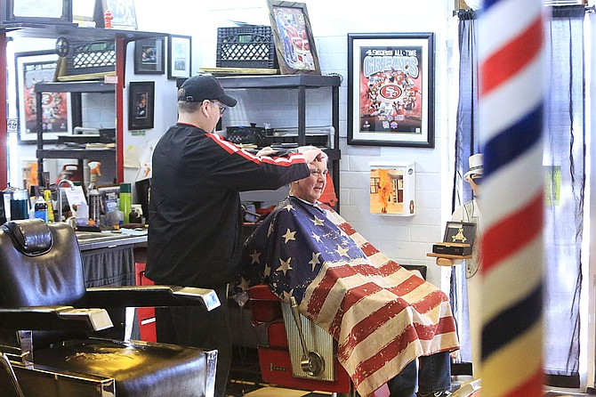 Jeff Nichols, owner of Capital Barbershop, cuts the hair of Steve Redmond of Gardnerville Friday afternoon. Nichols, an adamant 49ers fan, wore red and black while saying San Francisco will win Super Bowl LIV, 31-27.