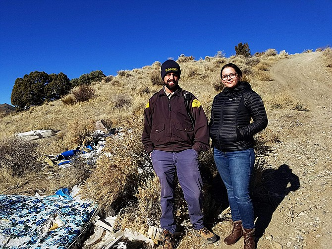 Park Ranger Tyler Kerver and Mackenzie Gargano, volunteer coordinator, stand near a mattress and other debris at a site where volunteers are needed to clean up on Jan. 20.