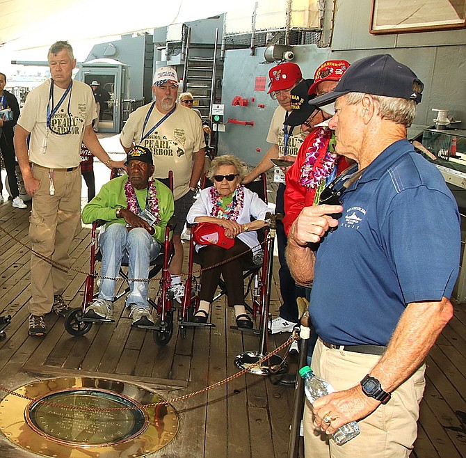 Veteran William Curry, second from right front row, listens to a guide tell the history of the signing of the permanent peace treaty aboard the USS Missouri.