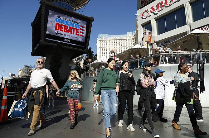 People walk near the Paris Las Vegas hotel casino, site of a Democratic presidential debate, Wednesday, Feb. 19, 2020, in Las Vegas. Nevada's first-in-the West presidential caucus puts the spotlight Saturday on a state that has swung increasingly blue over the last two decades. (AP Photo/John Locher)