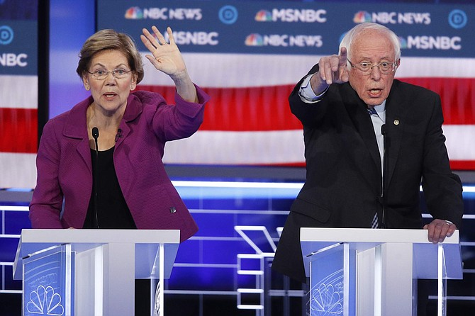 Democratic presidential candidates, Sen. Elizabeth Warren, D-Mass., left, and Sen. Bernie Sanders, I-Vt., try to answer a question during a Democratic presidential primary debate Wednesday, Feb. 19, 2020, in Las Vegas, hosted by NBC News and MSNBC. (AP Photo/John Locher)