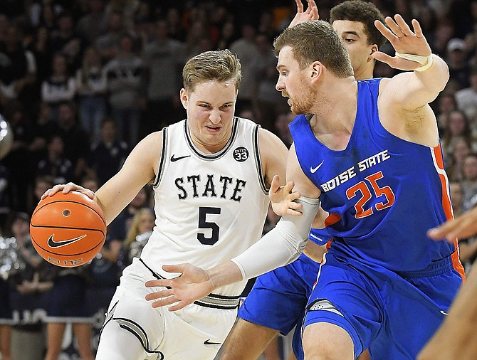Utah State guard Sam Merrill (5) drives to the basket as Boise State center Robin Jorch (25) defends during the second half of an NCAA college basketball game Saturday, Feb. 8, 2020, in Logan, Utah. (Eli Lucero/The Herald Journal via AP)
