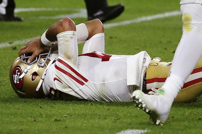 San Francisco 49ers quarterback Jimmy Garoppolo lays on the ground after being hit during the second half of Super Bowl 54.