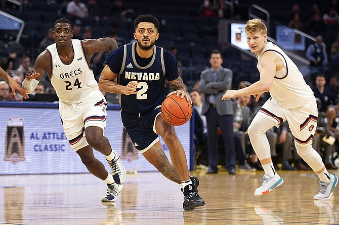 Nevada guard Jalen Harris (2) drives between Saint Mary's forwards Malik Fitts (24) and Matthias Tass during a game Dec. 21 in San Francisco.