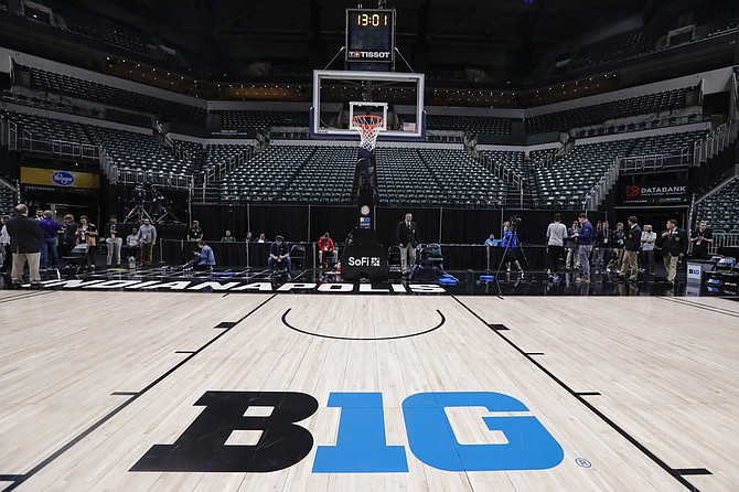 The seating area at Bankers Life Fieldhouse is empty as media and staff mill about, Thursday, March 12, 2020, in Indianapolis, after the Big Ten Conference announced that remainder of the men's NCAA college basketball games tournament was cancelled.