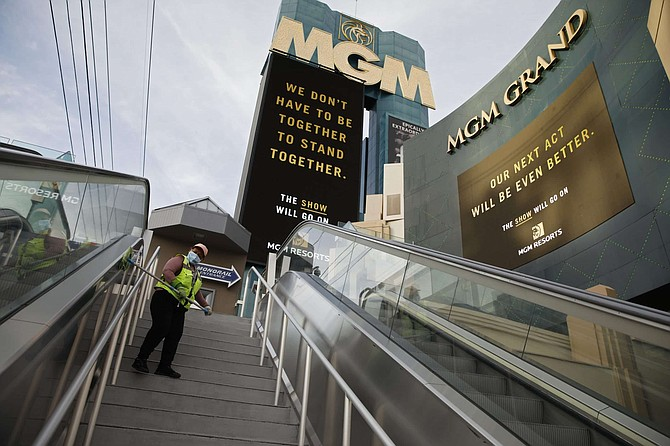 A worker cleans while wearing a face mask along the Las Vegas Strip devoid of the usual crowds after casinos and other business were shuttered due to the coronavirus outbreak Tuesday, March 31, 2020, in Las Vegas.