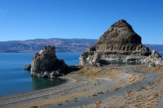 Pyramid Lake in the sunny afternoon, blue sky is reflected in the still waters of the mysterious lake of sacred Indian lands. Interesting rock formations against the bare Nevada landscape.
