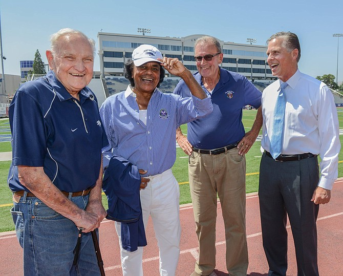 Entertainer Johnny Mathis laughs while donning a University of Nevada, Reno, cap during a gathering Saturday afternoon, August 22, 2015 at Mackay Stadium commemorating Mathis's record high jump while competing against UNR years ago. With Mathis are Dick Trachok, left, Ty Cobb and Greg Mosier, Dean of the College of Business.  Photo by Tim Dunn
