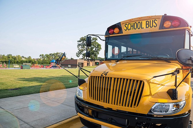 yellow school bus parked in front of school playground