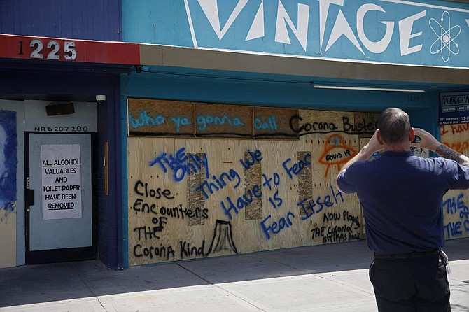 A man takes a picture of a business closed and boarded due to the concerns of the new coronavirus Wednesday, March 25, 2020, in Las Vegas.  Gov. Steve Sisolak on Tuesday night issued an emergency order banning gatherings of more than 10 people in the state indoors or outdoors, a more aggressive move to try to slow the spread of the coronavrius.