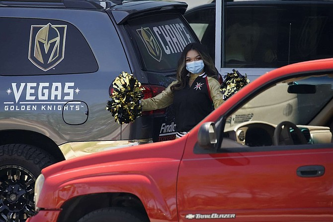 A cheerleader from the Vegas Golden Knights NHL hockey team cheer as a car drives up to pick up a purchase from their merchandise store at the team's practice facility Tuesday, May 5, 2020, in Las Vegas. The store had been closed due to the coronavirus but opened up for curbside service Tuesday.