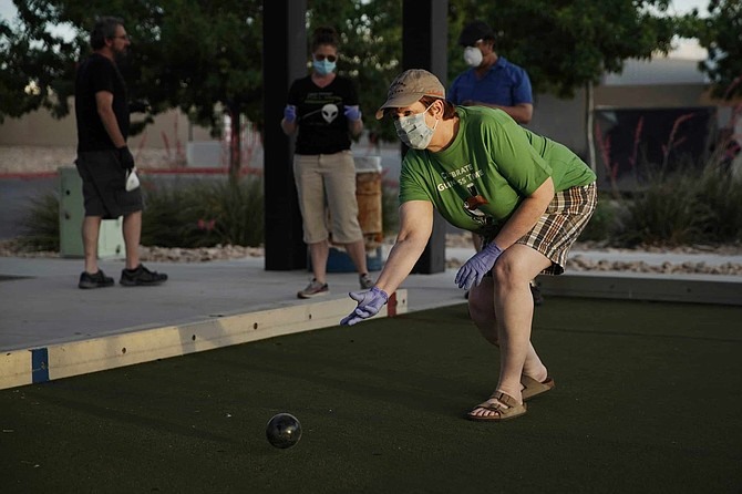 In this Wednesday, May 6, 2020, photo, Ginger Bruner plays bocce ball will friends at a park in Las Vegas. Bruner is a musician and hasn't worked since the coronavirus shutdown.