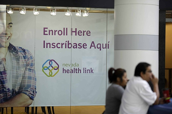 FILE - This Nov. 13, 2014 file photo people stand near an insurance store for Nevada Health Link at the Boulevard Mall in Las Vegas. Nevada's state-run health insurance marketplace added more than 6,000 people during a two-month window for those who lacked coverage but had not signed up during open enrollment last fall.