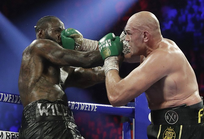 FILE - In this Feb. 22, 2020, file photo, Tyson Fury, of England, lands a right to Deontay Wilder, left, during a WBC heavyweight championship boxing match in Las Vegas. Boxing promoter Bob Arum says he plans to stage a card of five fights on June 9 at the MGM Grand. It's the first of a series of fights over the next two months at the Las Vegas hotel. A second fight card will be held two nights later. ESPN will televise both cards to kick off twice weekly shows at the hotel in June and July. The fights are pending approval of the Nevada Athletic Commission.
