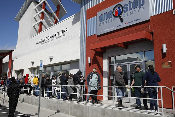 In this March 17, 2020, file photo, people wait in line for help with unemployment benefits at the One-Stop Career Center in Las Vegas. The coronavirus pandemic has been particularly brutal to the tourism-dependent economies of Nevada and Hawaii, lifting the unemployment rate in both states to about one-quarter of the workforce.