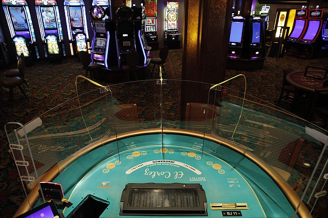 """FILE - In this May 13, 2020, file photo, an acrylic gaming barrier is installed at a gaming table to protect people from the coronavirus at the El Cortez hotel and casino as it remains shuttered due to the coronavirus in Las Vegas. Nevada gambling regulators said Tuesday, May 26, 2020, they may require the state's shuttered casinos to test all """"front line"""" resort workers for COVID-19, enact steps to prevent of the spread of illness and plan to isolate visitors and guests found to have the virus in order to get the OK to emerge from the coronavirus shutdown."""