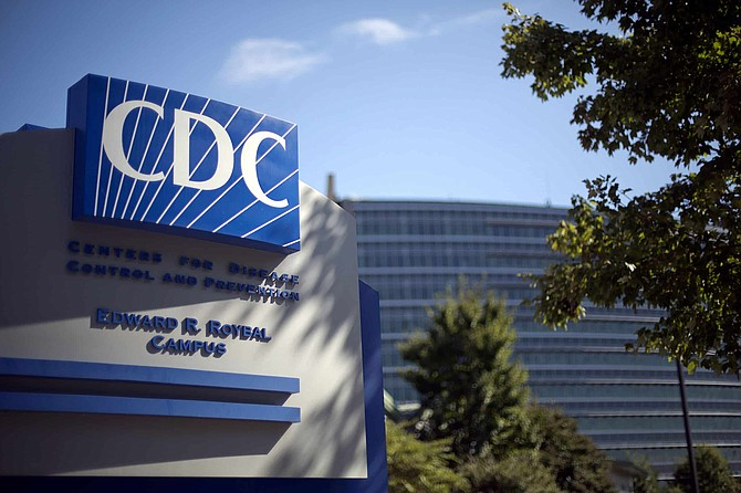 FILE - In this Oct. 8, 2013, file photo, a sign marks the entrance to the federal Centers for Disease Control and Prevention in Atlanta. In the United States, the nation with the most pandemic deaths, the reporting of vital coronavirus case and testing data is not keeping pace with its speedy spread. Public health officials nationwide lean too heavily on faxes, email and spreadsheets, sluggish and inefficient 20th-century tools.