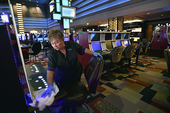 FILE - In this March 18, 2020, file photo, Antonia Garcia cleans slot machines inside the Planet Hollywood hotel-casino in Las Vegas. When shuttered casinos reopen in Nevada, patron counts will be cut in half, nightclubs will remain closed, convention groups will be limited and gamblers will have to keep safe distances apart. Nevada Gaming Control Board Chairwoman Sandra Douglass Morgan said Monday, May 4, 2020, the state is going to require a lot before letting casinos and resort operators reopen. Gov. Steve Sisolak has not announced a target date.