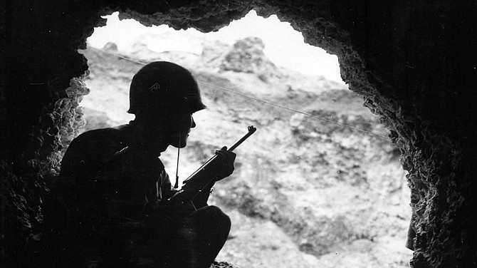 "American Marine uses an M1 Carbine to snipe at Japanese positions from an Okinawan cave. The American 10th Army's Action Report for the battle of Okinawa paid this understated compliment to the 32nd Army's defensive efforts: ""The continued development and improvement of cave warfare was the most outstanding feature of the enemy's tactics on Okinawa."" In their decision to defend the Shuri highlands across the southern neck of the island, General Ushijima and his staff had selected the terrain that would best dominate two of the island's strategic features: the port of Naha to the west, and the sheltered anchorage of Nakagusuku Bay (later Buckner Bay) to the east. As a consequence, the Americans would have to force their way into Ushijima's preregistered killing zones to achieve their primary objectives. Everything about the terrain favored the defenders. The convoluted topography of ridges, draws, and escarpments served to compartment the battlefield into scores of small firefights, while the general absence of dense vegetation permitted the defenders full observation and interlocking supporting fires from intermediate strongpoints. As at Iwo Jima, the Japanese Army fought largely from underground positions to offset American dominance in supporting arms. And even in the more accessible terrain, the Japanese took advantage of the thousands of concrete, lyre-shaped Okinawan tombs to provide combat outposts. There were blind spots in the defenses, to be sure, but finding and exploiting them took the Americans an inordinate amount of time and cost them dearly. The bitterest fighting of the campaign took place within an extremely compressed battlefield. The linear distance from Yonabaru on the east coast to the bridge over the Asa River above Naha on the opposite side of the island is barely 9,000 yards (8.2 kilometers). General Buckner initially pushed south with two Army divisions abreast. By 8 May he had doubled this commitment: two Army divisions of the XXIV Corps on the east, two Marine divisions of III Amphibious Corps on the west. Yet each division would fight its own desperate, costly battles against disciplined Japanese soldiers defending elaborately fortified terrain features. There was no easy route south."